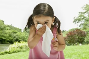 5 ways to alleviate seasonal allergy symptoms-little girl sneezing outdoors